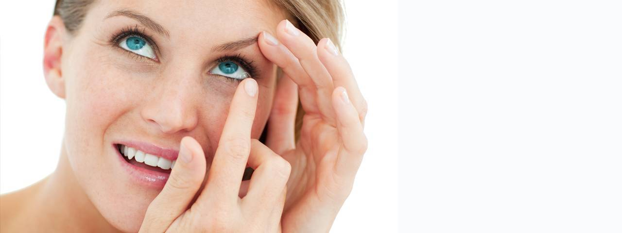 Optometrist, attractive blond putting in contact lens in O'Fallon, Wentzville, Hillsboro & Cottleville, MO